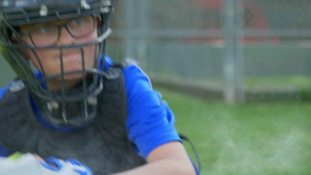 Boy catcher throwing the baseball in a little league game with mask. - Slow Motion