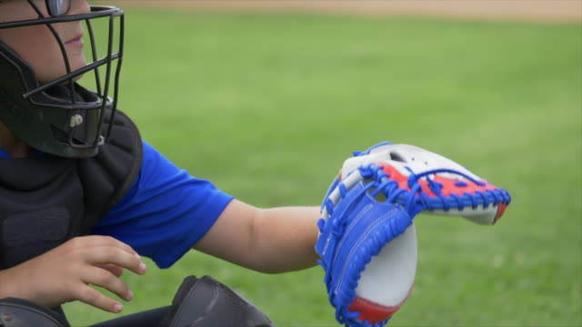 Boy catcher with American flag glove in a little league baseball game, catching the ball, red, white, blue, stars. - Slow Motion