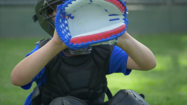 boy catcher with american flag glove in a little league baseball game, catching the ball, red, white, blue, stars. - slow motion - 野球用グローブ点の映像素材/bロール