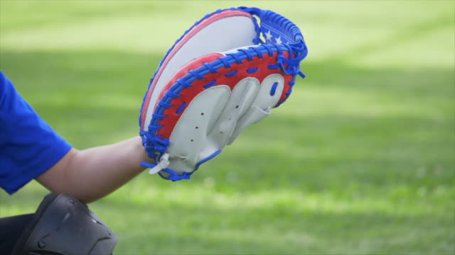 boy catcher with american flag glove in a little league baseball game, catching the ball, red, white, blue, smoking. - slow motion - 野球用グローブ点の映像素材/bロール