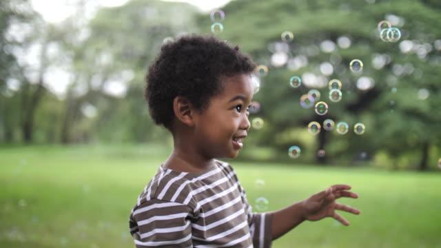vídeos y material grabado en eventos de stock de niño atrapa burbujas de jabón en parque público - 4 5 años