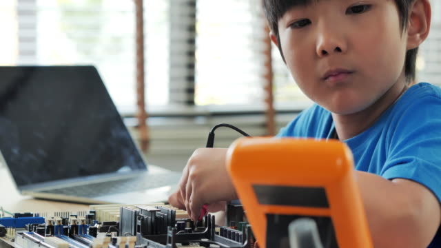 boy checking circuit board with multimeter at home and building a robot as a school science project.he is very satisfied with his work.happy smiling boy constructs technical.education, children, technology, science people concept - electrical equipment stock videos & royalty-free footage