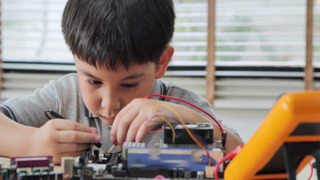 boy checking circuit board with multimeter at home and building a robot as a school science project.he is very satisfied with his work.happy boy constructs technical.education, children, technology, science people concept - electrical equipment stock videos & royalty-free footage