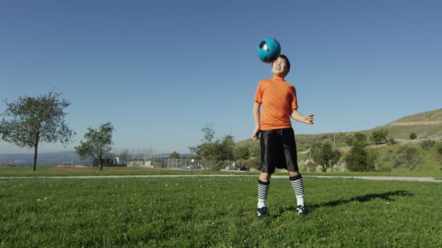 Boy chest traps soccer ball and runs