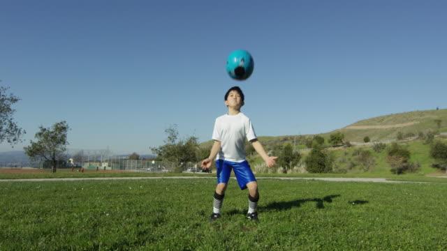 vídeos de stock, filmes e b-roll de boy chest traps soccer ball and runs - só um menino
