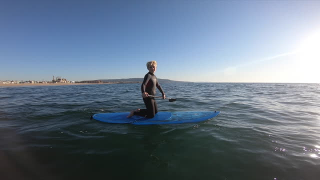 a boy child learning how to sup stand up paddleboarding on his knees. - kneeling stock videos & royalty-free footage