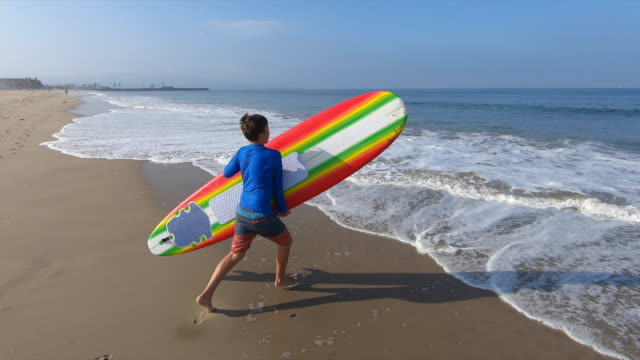 stockvideo's en b-roll-footage met a boy child learning how to surf surfing at the beach walking running with a surfboard. - vaardigheid