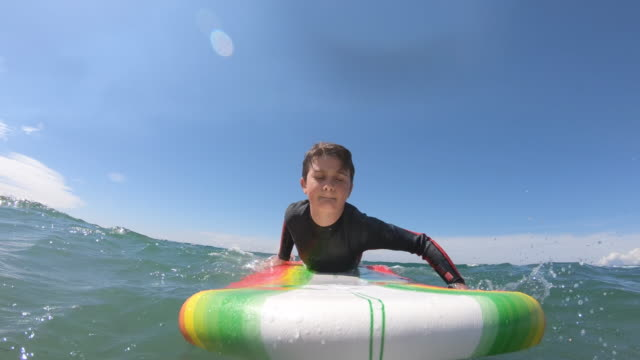 a boy child paddling on a surfboard and learning how to surf surfing. - slow motion - goal stock videos & royalty-free footage