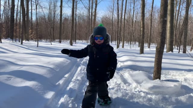 boy child snowshoeing outdoors in winter after snowstorm - eyewear stock videos & royalty-free footage