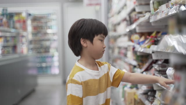 boy choosing cheaper food products at the convenience store, seoul, south korea - choosing stock videos & royalty-free footage