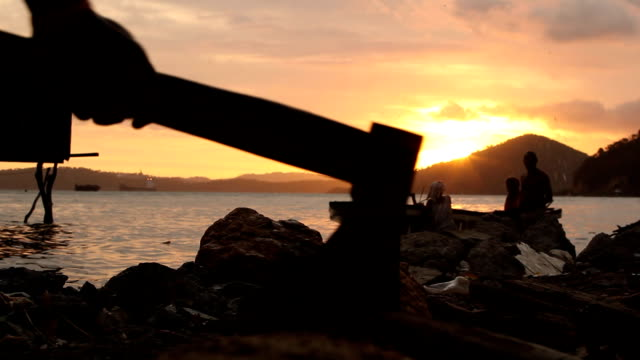 boy chopping wood with fishing boat in the background at sunset papua new guinea is an island located in oceania there are around 850 languages... - oceania stock videos and b-roll footage