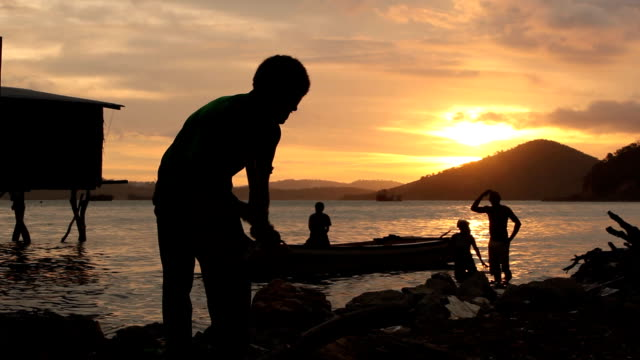 boy chopping wood with fishing boat in the background at sunset . papua new guinea is an island located in oceania. there are around 850 languages... - oceania stock videos & royalty-free footage