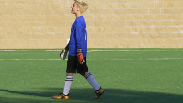 a boy clapping while playing youth soccer football goalie goalkeeper on a turf grass field. - soccer goalkeeper stock videos & royalty-free footage