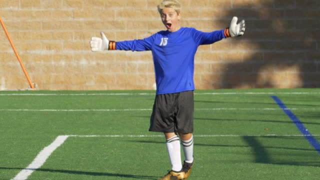 a boy clapping while playing youth soccer football goalie goalkeeper on a turf grass field. - slow motion - soccer goalkeeper stock videos & royalty-free footage