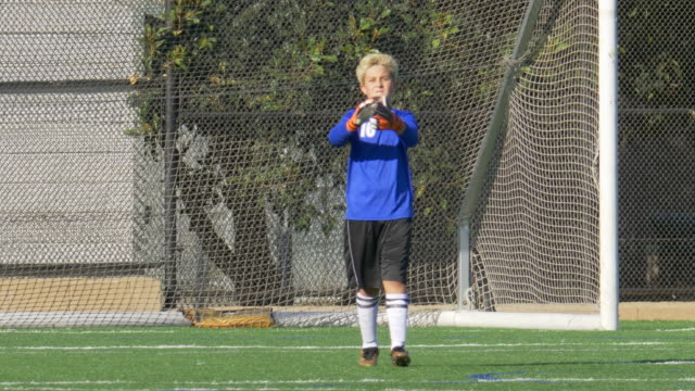a boy clapping while playing youth soccer football goalie goalkeeper on a turf grass field. - slow motion - scoring a goal stock videos & royalty-free footage