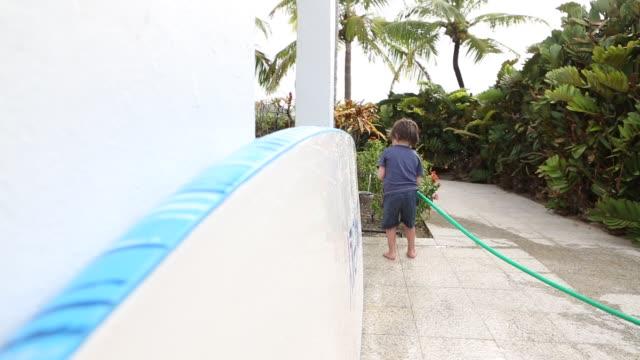 boy cleaning paddle board - sonnenschild stock-videos und b-roll-filmmaterial