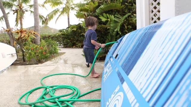 boy cleaning paddle board