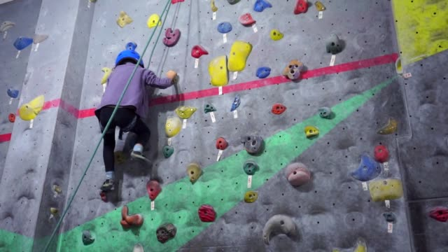 boy climbing on a wall in an indoor climbing center. - climbing wall stock videos & royalty-free footage