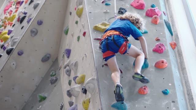 vídeos y material grabado en eventos de stock de niño escalando en la pared de escalada - escalada libre