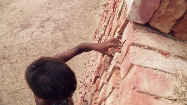 Boy climbing on the bricks, Haryana, India