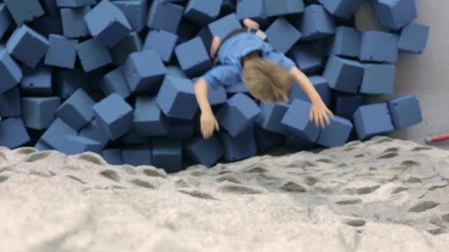 WS Boy climbing rock wall and falling down onto foam blocks / Vancouver, British Columbia, Canada
