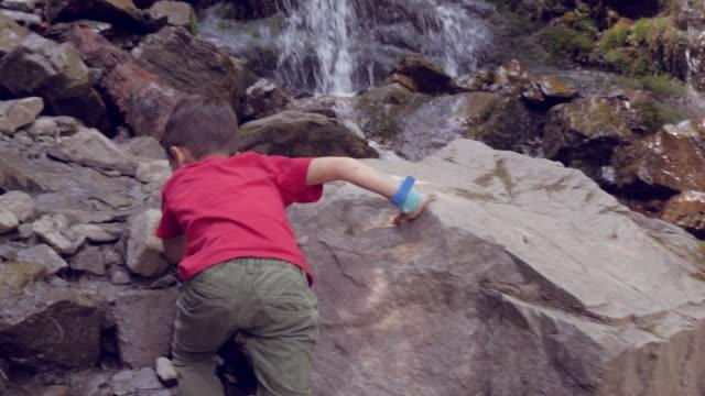 滝の岩を登る少年