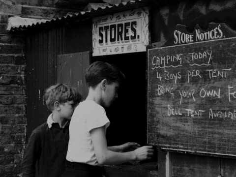 boy collects a spade from a youth club store hut. 1957. - youth club stock videos & royalty-free footage