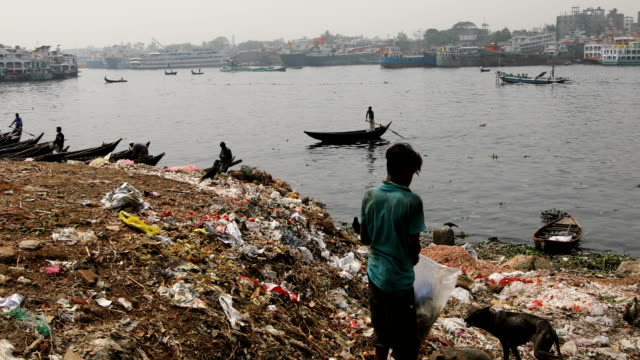a boy collects usable goods from dust in the buriganga river in dhaka bangladesh on march 21 2020 the chemical waste of mills and factories... - population explosion stock videos & royalty-free footage