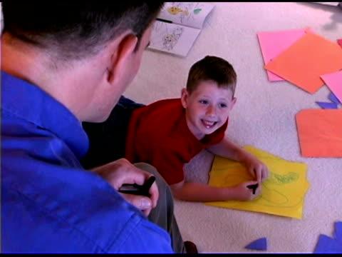 vídeos y material grabado en eventos de stock de boy coloring and talking father - hombres de mediana edad