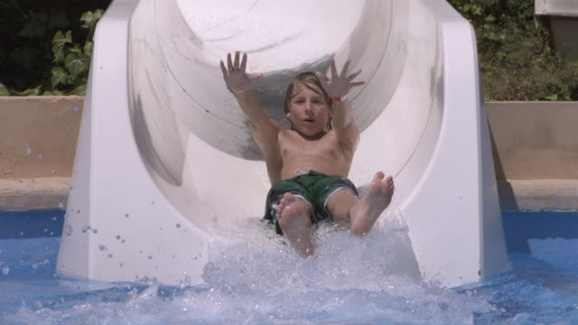Boy coming down water chute, to camera