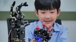 Boy constructs and programmes on computer and building a robot arm as a school science project.He is very satisfied with his work.Education,technology,teamwork,science and people concept.Education Topics