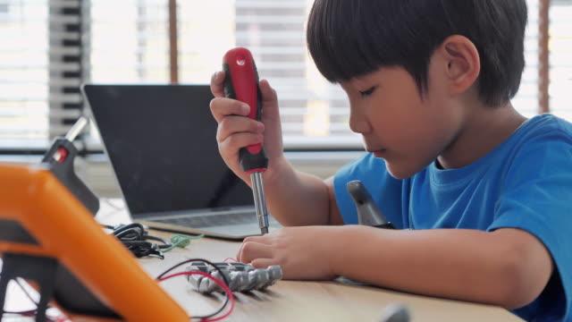 vídeos y material grabado en eventos de stock de boy construye y programas en el ordenador en casa y la construcción de un brazo robótico como un proyecto de ciencias escolares. él está muy satisfecho con su trabajo. educación, niños, tecnología, ciencia de la gente concepto - herramienta de mano