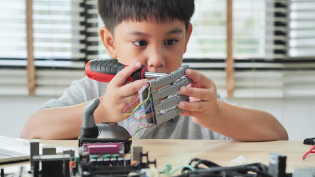 boy constructs and programmes on computer at home and building a robot arm as a school science project.he is very satisfied with his work.education, children, technology, science people concept - manufacturing machinery stock videos & royalty-free footage