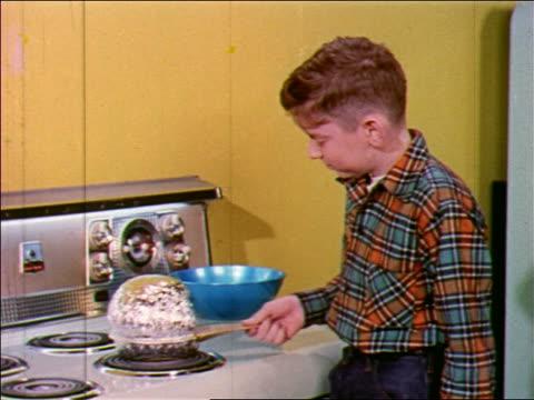 1955 boy cooking jiffy pop popcorn on stove / industrial - アルミホイル点の映像素材/bロール