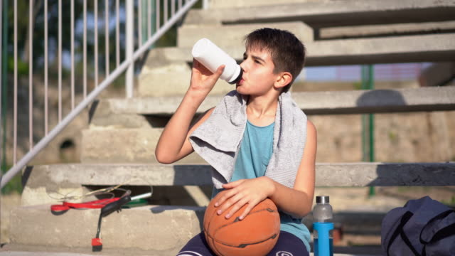 boy cooling down after basketball training - basketball sport stock videos & royalty-free footage