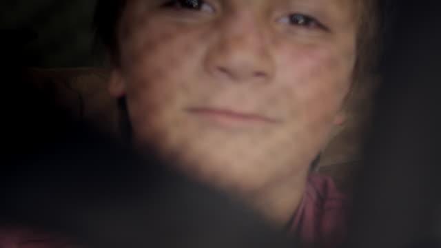 boy covers camera lens with hat - berretto da baseball video stock e b–roll