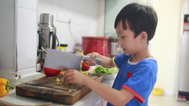 boy cutting brocoli for cooking at domestic kitchen - utensil stock videos & royalty-free footage