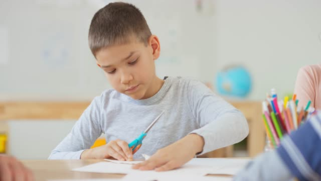 boy cutting paper with scissors sitting at the table - scissors stock videos & royalty-free footage