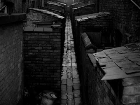boy cycles along a narrow alleyway between terraced slum houses in salford - narrow stock videos & royalty-free footage