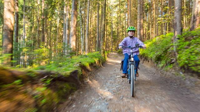 cu boy cycling through forest - スポーツヘルメット点の映像素材/bロール