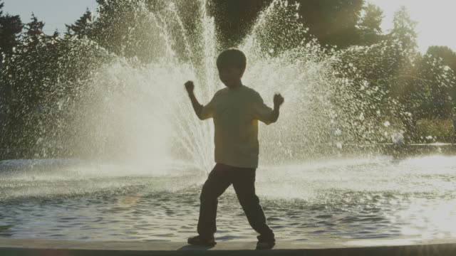 Boy dances near park fountain