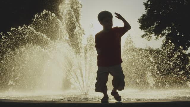 vídeos y material grabado en eventos de stock de boy dances near park fountain - fuente estructura creada por el hombre