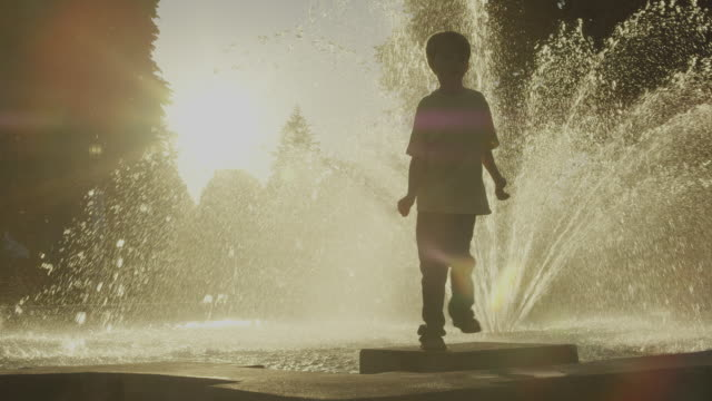 stockvideo's en b-roll-footage met boy dances near park fountain - fontein