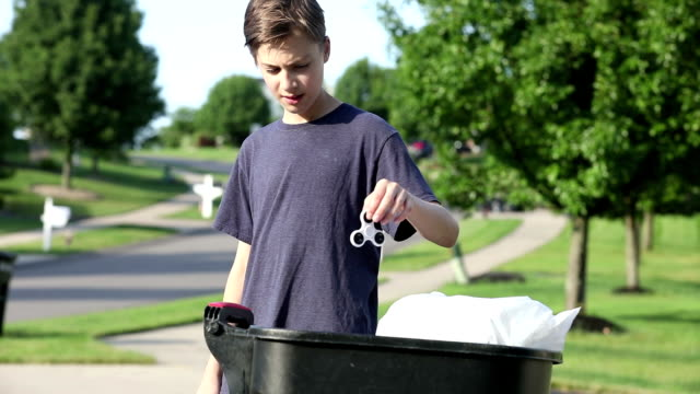 Boy Deciding To Throw Fidget Spinner In Trash
