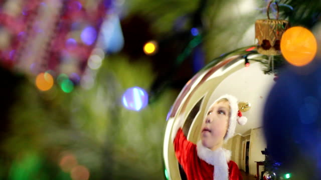 vídeos de stock e filmes b-roll de menino decorates the árvore de natal, brinquedos - chapéu do pai natal