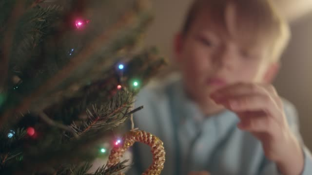 boy decorating christmas tree in home - decorating the christmas tree stock videos & royalty-free footage