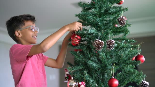 boy decorating christmas tree - decoration stock videos & royalty-free footage