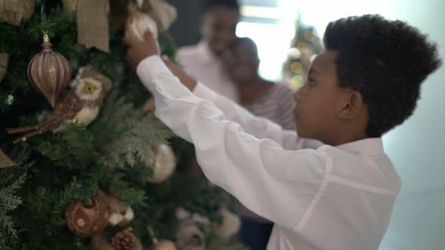 junge schmücken weihnachtsbaum - weihnachtskrippe stock-videos und b-roll-filmmaterial