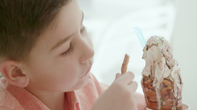 boy digging in soft serve ice cream with wafer at the table - excess stock videos & royalty-free footage