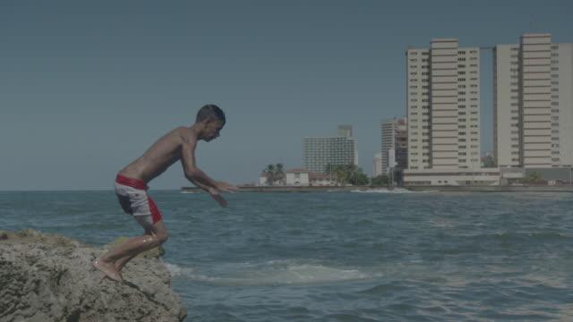boy dives off cliff into ocean - nur teenager stock-videos und b-roll-filmmaterial